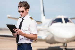 A male pilot stands outside of a corporate jet aircraft, using a modern digital tablet to update his flight plan and preflight checklist.